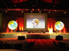 The middle section of a 50m wide, 7 screen stage-set done for the IIA SA Southern African Conference in 2015 with 3D animated globe spheres on either side of the centre screen